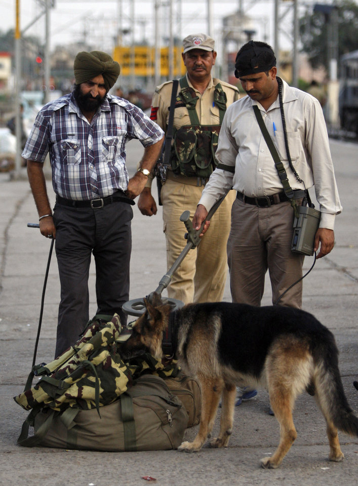Photo - Security officers, along with a sniffer dog, inspect luggage at a railway station in Jammu, india, Thursday, July 3, 2014. Security has been beefed up ahead of Indian prime minister Narendra Modi's visit to the state of Jammu and Kashmir, Police said. (AP Photo/Channi Anand)