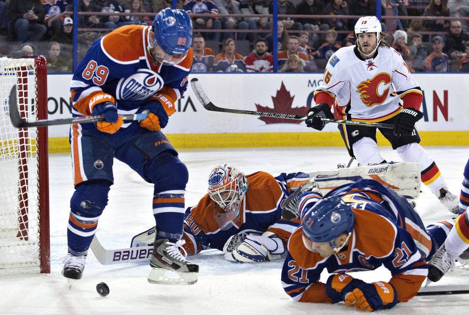 Photo - Calgary Flames' Kevin Westgarth (15) looks for the rebound as Edmonton Oilers goalie Ilya Bryzgalov (80) makes the save as Sam Gagner (89) and Andrew Ference (21) defend during the first period of an NHL hockey game, Saturday, March 1, 2014 in Edmonton, Alberta. (AP Photo/The Canadian Press, Jason Franson)