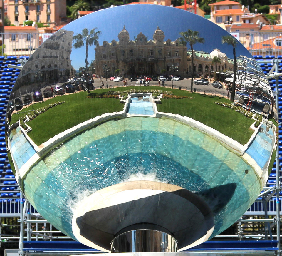 """Photo - This May 13, 2013 photo shows the sculpture """"Sky Mirror,"""" which faces the Monte Carlo Casino in Monaco. The large circular mirror reflects the building  and is one of a number of free things to see and do in Monaco. (AP Photo/Michelle Locke)"""