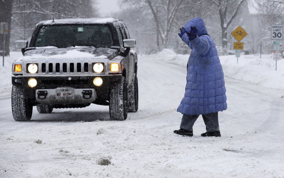 Photo - A woman raises her hands as she crosses the street in Chicago on Sunday, Jan. 5, 2014. Sunday night temperatures will drastically drop to about minus 20 degrees. (AP Photo/Nam Y. Huh)