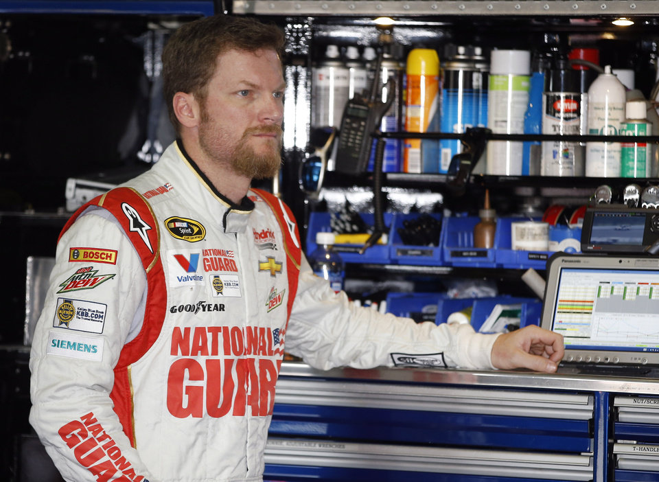 Photo - Dale Earnhardt Jr. waits in the garage stall as his car is adjusted during a practice session for Sunday's NASCAR Sprint Cup Series auto race at Pocono Raceway, Friday, Aug. 1, 2014, in Long Pond, Pa. (AP Photo/Matt Slocum)