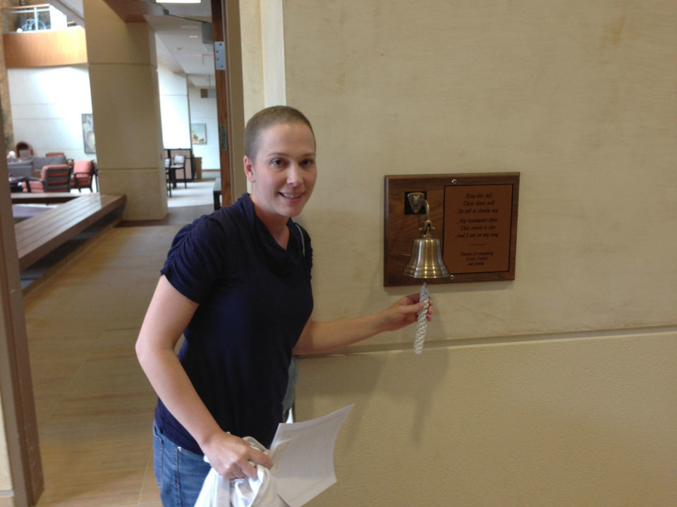Photo - Jenny Herzberger rings the bell after her last radiation treatment at the Stephenson Cancer  Center in Oklahoma City on Sept. 13, 2013. PHOTO PROVIDED
