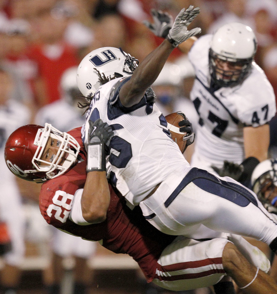 Photo - OU's Travis Lewis brings down Utah State's Kerwynn Williams during the second half of the college football game between the University of Oklahoma Sooners (OU) and Utah State University Aggies (USU) at the Gaylord Family-Oklahoma Memorial Stadium on Saturday, Sept. 4, 2010, in Norman, Okla.   Photo by Bryan Terry, The Oklahoman