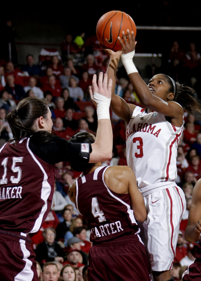 Photo - OU's Aaryn Ellenberg (3) shoots the ball in front of Texas A&M's Maryann Baker (15) and Texas A&M's Sydney Carter (4) during the Big 12 women's basketball game between the University of Oklahoma and Texas A&M at Lloyd Noble Center in Norman, Okla., Wednesday January 26, 2011.  Photo by Bryan Terry, The Oklahoman