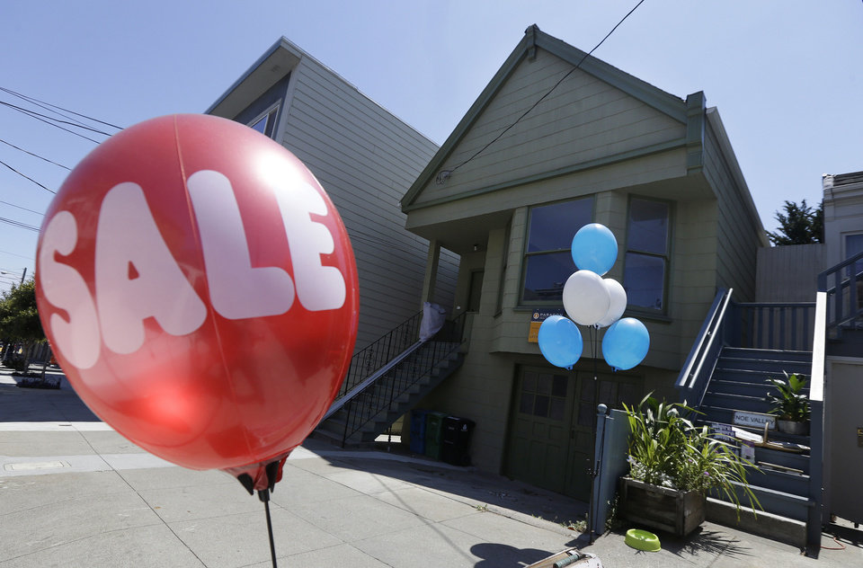 Photo - A sale balloon for a nearby store is shown next to a property in the Noe Valley neighborhood just sold for $1.8 million in cash, $600,000 more than its asking price, in San Francisco, Wednesday, July 30, 2014. In the souped-up world of San Francisco real estate, where the median selling price for homes and condominiums hit seven figures for the first time last month, the cool million that would fetch a mansion on a few acres elsewhere will now barely cover the cost of an 800-square-foot starter home. (AP Photo/Jeff Chiu)
