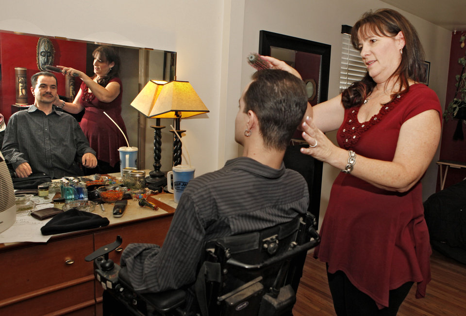 Photo - Brandon Coats' mother Donna brushes Brandon's hair at his home in Denver on Thursday, Dec. 6, 2012. The Colorado case of Brandon Coats is giving employers pause. Coats, 33, was a telephone operator for Dish Network. Paralyzed as a teenager in a car crash, he's also been a medical marijuana patient in Colorado since 2009. He was fired in 2010 for failing a company drug test, though the employer didn't claim he was ever impaired on the job. Coats sued, and the case is pending before the Colorado Court of Appeals. The case will test the bounds of Colorado's Lawful Off-Duty Activities Law, which says workers can't be dismissed for legal behavior off the clock. It was enacted in 2007 to protect tobacco users. (AP Photo/Ed Andrieski)