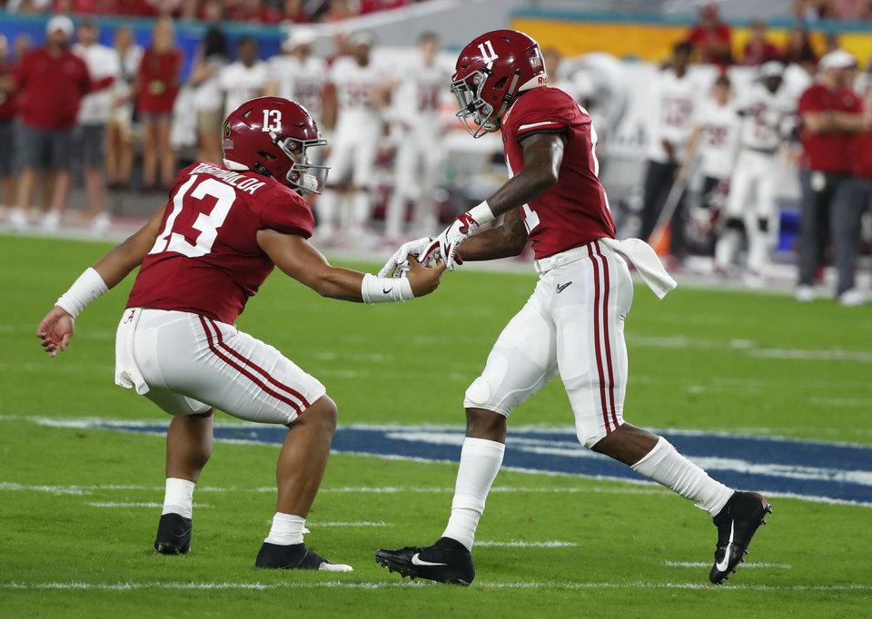 Photo - Alabama quarterback Tua Tagovailoa (13) congratulates wide receiver Henry Ruggs III (11) after Ruggs scored a touchdown, during the first half of the Orange Bowl NCAA college football game against Oklahoma, Saturday, Dec. 29, 2018, in Miami Gardens, Fla. (AP Photo/Wilfredo Lee)