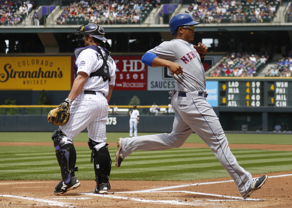 Photo - New York Mets' Juan Legares, front, scores on a single by Curtis Granderson as Colorado Rockies catcher Michael McKenry waits for the throw from the outfield in the first inning of a baseball game in Denver on Sunday, May 4, 2014. (AP Photo/David Zalubowski)