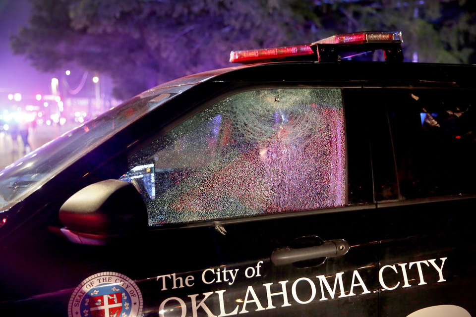 Photo - Oklahoma City Police car is damaged in front the station in Oklahoma City, Saturday, May 30, 2020. The protest was in response to the death of George Floyd. [Sarah Phipps/The Oklahoman]