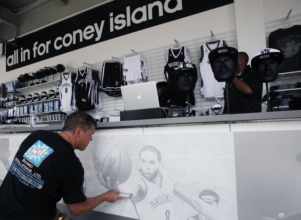 Photo - FILE - In this May 23, 2013 file photo, Barry Schmid applies a photo display inside a shop that carries apparel featuring the NBA basketball team Brooklyn Nets in the Coney Island neighborhood of Brooklyn in New York. New York Mayor Bill de Blasio has placed his city's bid for the Democratic Convention in Brooklyn, at the Barclays Center, home of the Brooklyn Nets. Brooklyn's cultural touchstones have evolved from Ralph Kramden to Spike Lee and Jay-Z and the black-and-white logo and color scheme of the Brooklyn Nets has become a fashion staple even for non-basketball fans. (AP Photo/Mark Lennihan, File)
