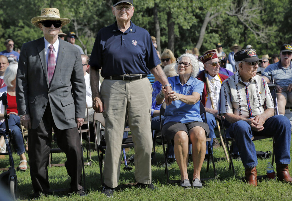 Photo -  A pair of military veterans stand as the emcee invites soldiers from the nation's various wars to stand during the 45th Infantry Division Museum's annual Memorial Day Ceremony on Monday. Louise Johnson, seated, holds the hand of her 98 year-old husband, World War II veteran Burton J. Johnson, who served in the US Army. The Johnsons have been coming to the Memorial Day ceremony for at least 20 years, Louise Johnson said. At left is Maj. Gen. (USAF-Retired) William Bowden. He is a former commander of the Oklahoma City Air Logistics Center at Tinker Air Force Base in Oklahoma City. He served in the Vietnam War as navigator and bombardier on B-52 aircraft. Bowden has been inducted in the Oklahoma Military Hall of Fame.[Photo by Jim Beckel, The Oklahoman]