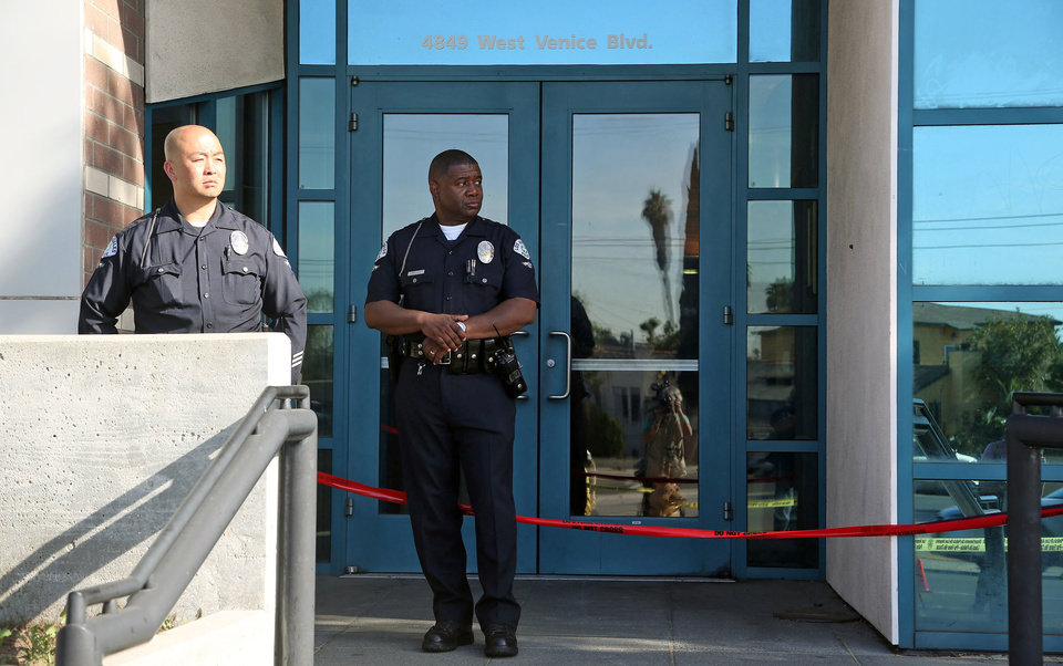 Photo - Los Angeles police officers stand outside the West Traffic Division station Tuesday, April 8, 2014, after an officer was shot and wounded inside the station Monday evening. A gunman who opened fire inside the police station, hitting one officer several times, was hospitalized early Tuesday in critical condition after he was wounded in the ensuing gunbattle, authorities said.  (AP Photo/Nick Ut )