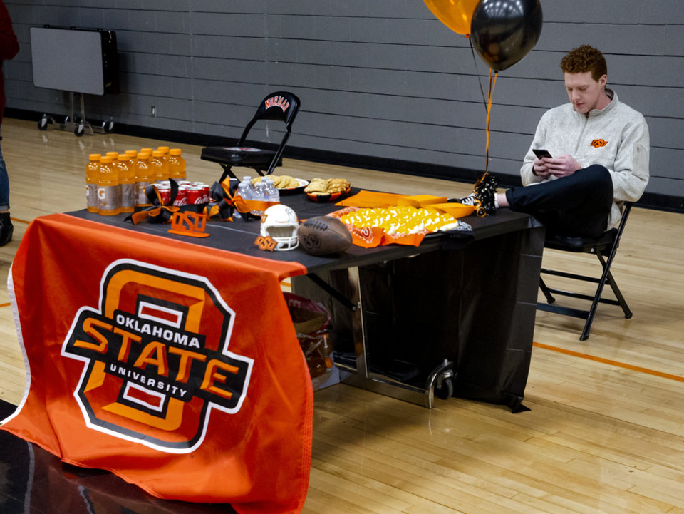 Photo - Oklahoma State University signee Cole Thompson uses his phone as he waits for the start of a national signing day ceremony for football at Norman High School in Norman Okla. on Wednesday, Dec. 18, 2019.   [Chris Landsberger/The Oklahoman]