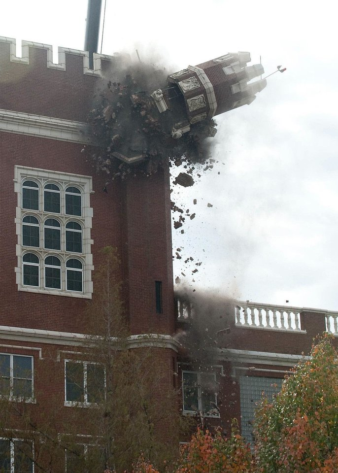 A turret crashes from the side of Benedictine Hall at St. Gregory's University after it was pushed down for safety reasons following the Nov. 5, 2011, earthquake that damaged the building. Photo provided