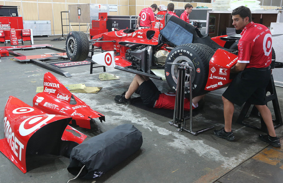 IndyCar team Chip Ganassi mechanics work in the garage area at the racetrack in Sao Paulo, Brazil, Thursday, May 2, 2013.  Brazil will host the 4th race of the Indy Car season on May 5. (AP Photo/Andre Penner)