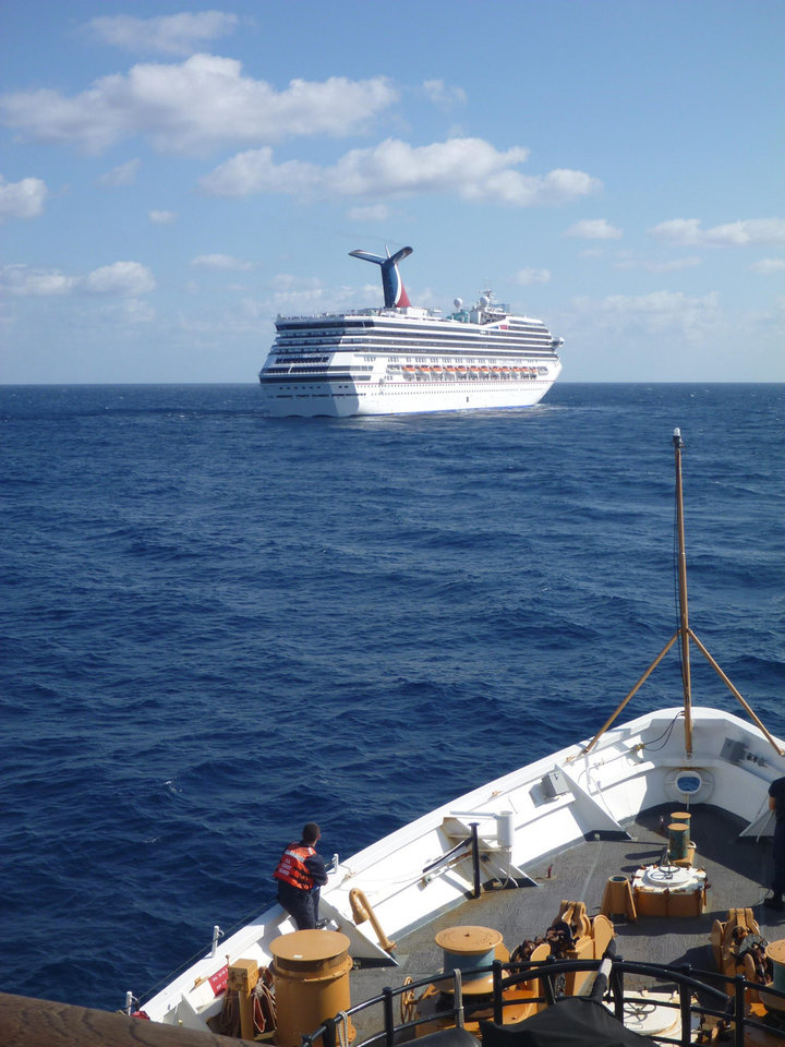 Photo - In this image released by the U.S. Coast Guard on Feb. 11, 2013, the Coast Guard Cutter Vigorous patrols near the cruise ship Carnival Triumph in the Gulf of Mexico, Feb. 11, 2013. The Carnival Triumph has been floating aimlessly about 150 miles off the Yucatan Peninsula since a fire erupted in the aft engine room early Sunday, knocking out the ship's propulsion system. No one was injured and the fire was extinguished. (AP Photo/U.S. Coast Guard- Lt. Cmdr. Paul McConnell)