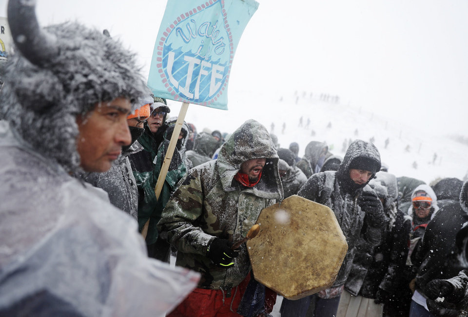 Photo - Steven Paul, a Nez Perce Native American from Portland, Ore., drums during a march with military veterans and tribal elders outside the Oceti Sakowin camp where people have gathered to protest the Dakota Access oil pipeline in Cannon Ball, N.D., Monday, Dec. 5, 2016. (AP Photo/David Goldman)