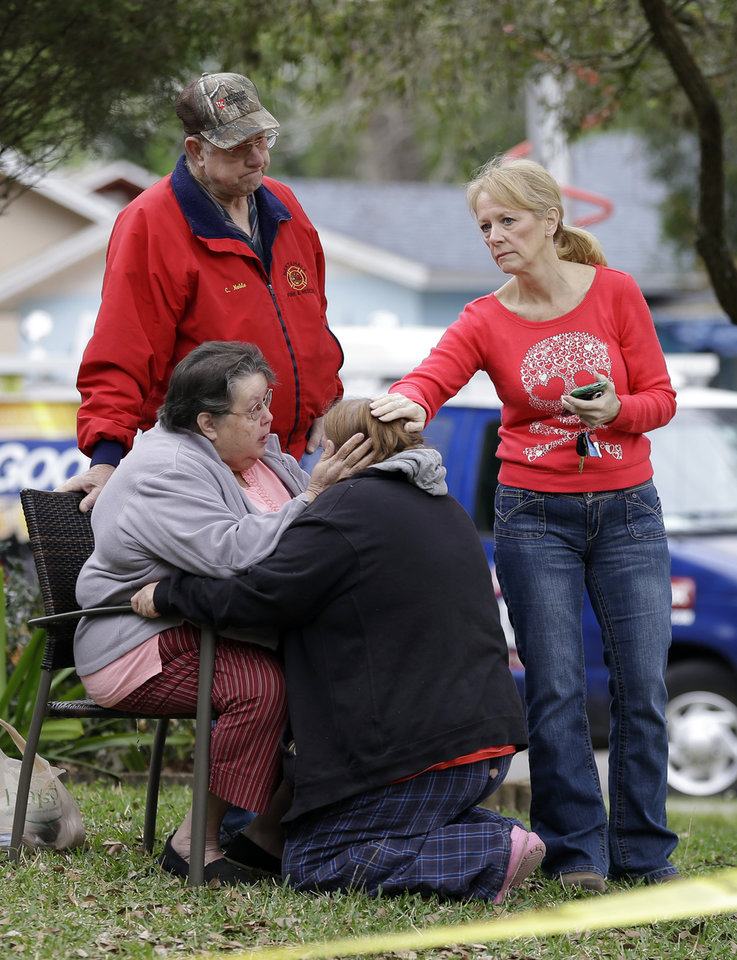 Photo - Family members console each other near the home where Jeff Bush disappeared as a large sinkhole opened under the bedroom of his house on  Friday, March 1, 2013, in Seffner, Fla.  Jeremy Bush told rescue crews he heard a loud crash near midnight Thursday, then heard his brother screaming.  There's been no contact with Jeff Bush since then, and neighbors on both sides of the home have been evacuated. (AP Photo/Chris O'Meara)