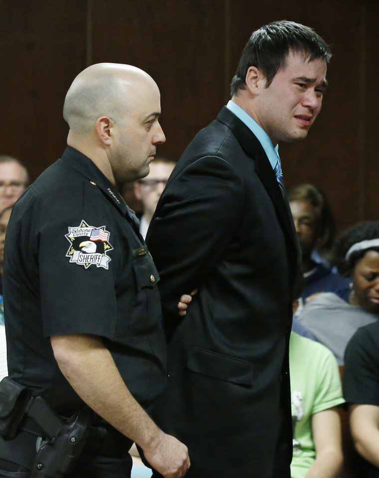 Photo - Daniel Holtzclaw, right, looks at the jury as he is escorted from the courtroom after the verdicts in his trial in Oklahoma City, Thursday, Dec. 10, 2015. Holtzclaw, a former Oklahoma City police officer, was facing dozens of charges alleging he sexually assaulted 13 women while on duty. Holtzclaw was found guilty on a number of counts. (AP Photo/Sue Ogrocki, Pool)