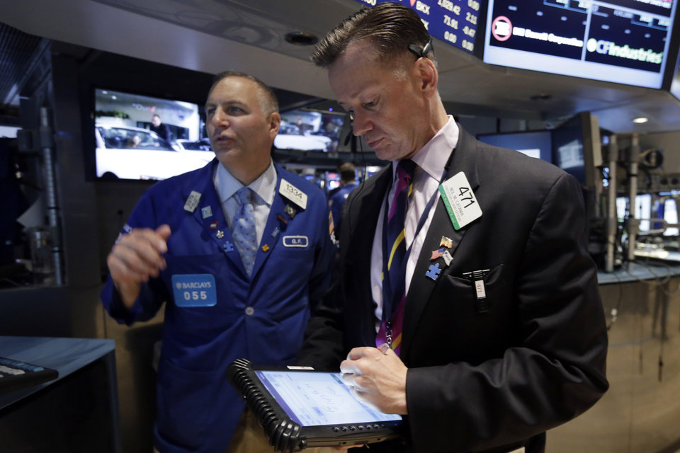 Photo - Trader Neil Catania, right, works on the floor of the New York Stock Exchange Tuesday, July 8, 2014. U.S. stocks are opening lower for a second day in a row as investors position themselves for corporate earnings reports. (AP Photo/Richard Drew)