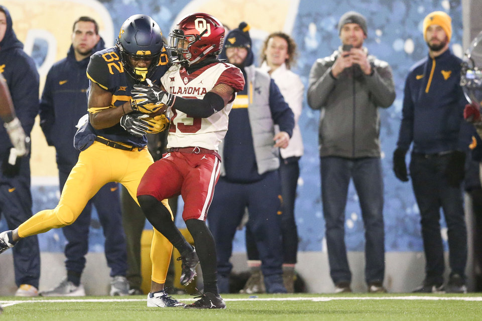 Photo - West Virginia Mountaineers wide receiver Dominique Maiden (82) catches a pass over Oklahoma Sooners cornerback Tre Norwood (13) during the NCAA football game between the Oklahoma Sooners and the West Virginia Mountaineers at Mountaineer Field at Milan Puskar Stadium in Morgantown, W.Va on Friday, November 23, 2018. IAN MAULE/Tulsa World