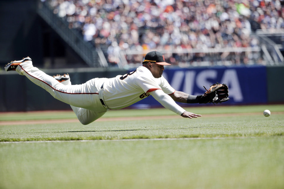 Photo - San Francisco Giants third baseman Pablo Sandoval makes a diving attempt on a bunt from Milwaukee Brewers' Carlos Gomez during the first inning of a baseball game on Sunday, Aug. 31, 2014, in San Francisco. Gomez got an infield single on the play. (AP Photo/Marcio Jose Sanchez)