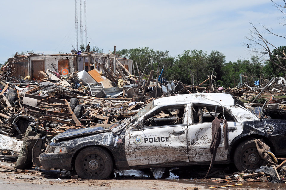 Photo - A ruined Del City police car sits in the street in front of destroyed homes on Kings Manor Rd. in Moore, Okla. on May 22, 2013. Photo by KT King, The Oklahoman