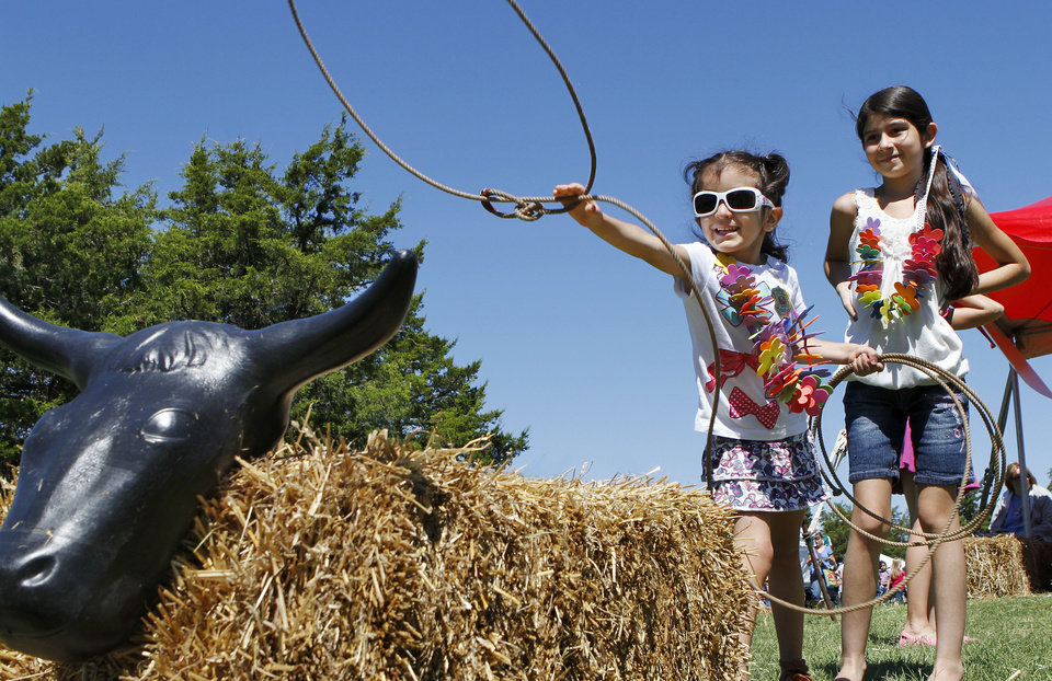 Photo - Citalaly Martinez tosses a rope toward the head of a plastic roping dummy at the 2012 Septemberfest on the grounds of the Governor's Mansion. PHOTO BY JIM BECKEL, THE OKLAHOMAN ARCHIVE  Jim Beckel