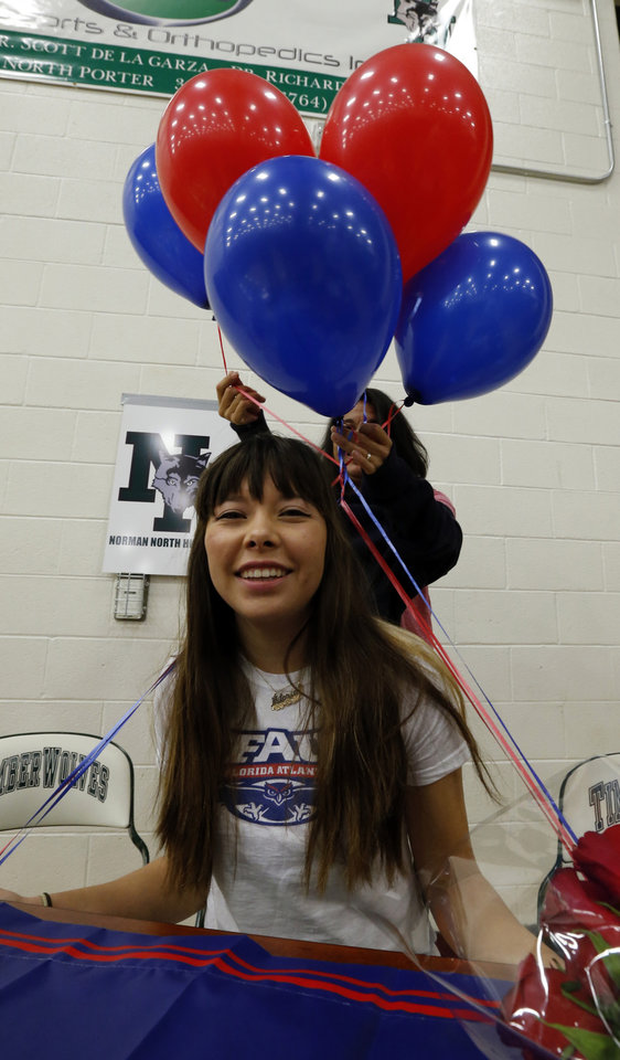 Photo - Victoria VanHootegem gets a balloon decoration from her mother Carmen as she signs a letter of intent to play soccer for Florida Atlantic University at signing day ceremonies at Norman North High School on Wednesday, Feb. 5, 2014 in Norman, Okla.  Photo by Steve Sisney, The Oklahoman
