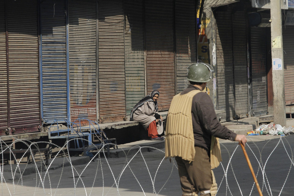 A Kashmiri woman sits outside closed shops as an Indian paramilitary soldier stands near barbed wire set up as road block on the fourth consecutive day of curfew imposed after the execution of a Kashmiri man convicted in a deadly 2001 attack on India's Parliament in Srinagar, India, Tuesday, Feb. 12, 2013. Mohammed Afzal Guru was hanged in New Delhi early Saturday. Ahead of the execution, authorities had anticipated anti-India protests and ordered people in most of the Indian-held part of the disputed Kashmir region to remain indoors indefinitely. (AP Photo/Mukhtar khan)