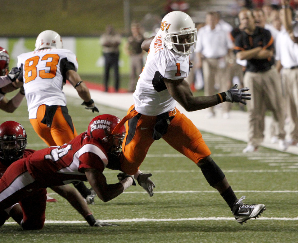 Photo - OSU's Joseph Randle tries to get past  Louisiana-Lafayette's Lionel Stokes during the football game between the University of Louisiana-Lafayette and Oklahoma State University at Cajun Field in Lafayette, La., Friday, October 8, 2010. Photo by Bryan Terry, The Oklahoman