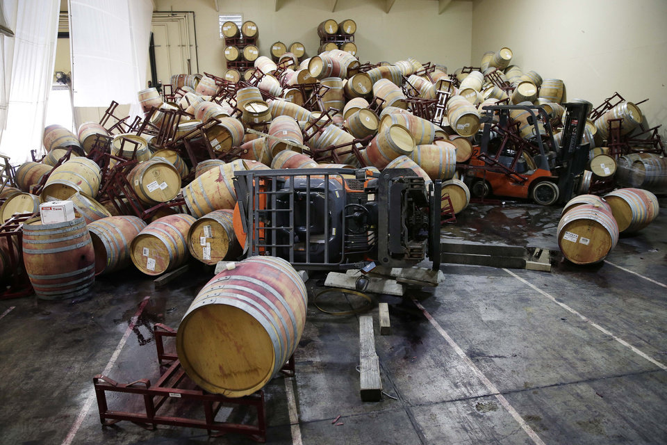 Photo - Some of the hundreds of earthquake damaged wine barrels cover and toppled a pair of forklifts at the Kieu Hoang Winery, Monday, Aug. 25, 2014, in Napa, Calif. A powerful earthquake that struck the heart of California's wine country caught many people sound asleep, sending dressers, mirrors and pictures crashing down around them and toppling wine bottles in vineyards around the region. The magnitude-6.0 quake struck at 3:20 a.m. PDT Sunday near the city of Napa. (AP Photo/Eric Risberg)