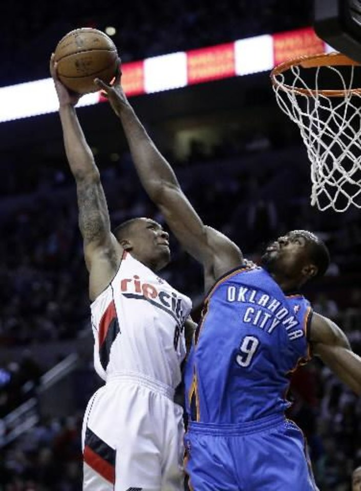 Oklahoma City Thunder forward Serge Ibaka, right, blocks a shot by Portland Trail Blazers guard Damian Lillard during the second half of an NBA basketball game in Portland, Ore., Friday, April 12, 2013. The Thunder won 106-90. (AP)