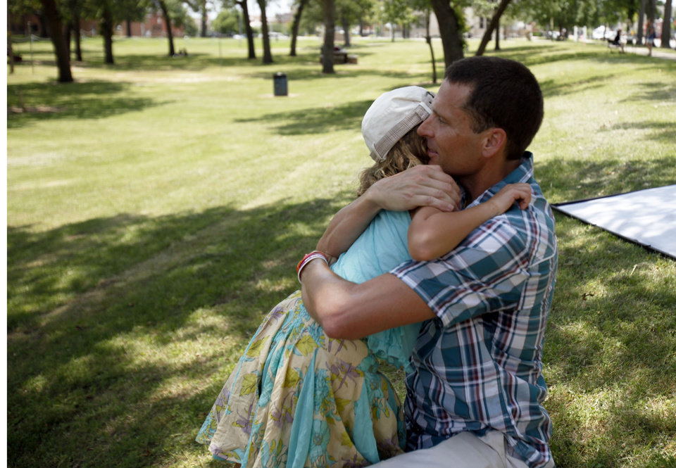 Vivienne Harr, 9, of Fairfax, Calif., gives her father, Eric Harr, a hug at her Make A Stand lemonade stand Friday in Woodland Park in Shawnee. Photo by Aliki Dyer, The Oklahoman <strong>Aliki Dyer - The Oklahoman</strong>