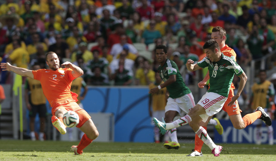 Photo - Netherlands' Ron Vlaar (2) stops a shot by Mexico's Oribe Peralta, right, during the World Cup round of 16 soccer match between the Netherlands and Mexico at the Arena Castelao in Fortaleza, Brazil, Sunday, June 29, 2014. (AP Photo/Marcio Jose Sanchez)