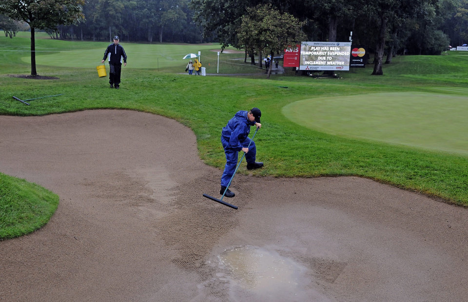 Photo - Volunteers Kurt Galisdorfer,right, and Heather Hemming remove water from a sand trap on the second hole during a rain delay in the final round of the BMW Championship golf tournament at Conway Farms Golf Club in Lake Forest, Ill., Sunday, Sept. 15, 2013. (AP Photo/Matt Marton)
