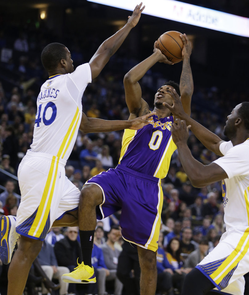 Los Angeles Lakers' Nick Young (0) shoots between Golden State Warriors' Harrison Barnes, left, and Draymond Green during the first half of an NBA basketball game Saturday, Dec. 21, 2013, in Oakland, Calif. (AP Photo/Ben Margot)