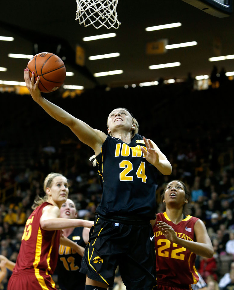 Photo - Iowa guard Jaime Printy (24) puts up a shot in front of Iowa State center Anna Prins (55) and guard/forward Brynn Williamson (22) during the first half an NCAA college basketball game Thursday, Dec. 6, 2012 at Carver-Hawkeye Arena in Iowa City, Iowa.  (AP Photo/The Gazette,Brian Ray)