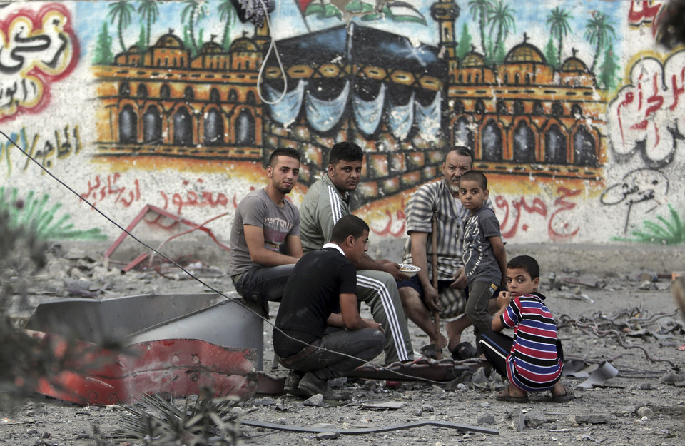 Photo - Palestinians rest amid the rubble of the 15-story Basha Tower that was leveled in early morning Israeli airstrikes, in Gaza City, Tuesday, Aug. 26, 2014. Israel bombed two Gaza City high-rises with dozens of homes and shops Tuesday, collapsing the 15-story Basha Tower and severely damaging the Italian Complex in a further escalation in seven weeks of cross-border fighting with Hamas. Both buildings were evacuated after receiving warnings of impending strikes. The wall painting depicts the pilgrimage to Mecca or Haj. (AP Photo/Khalil Hamra)