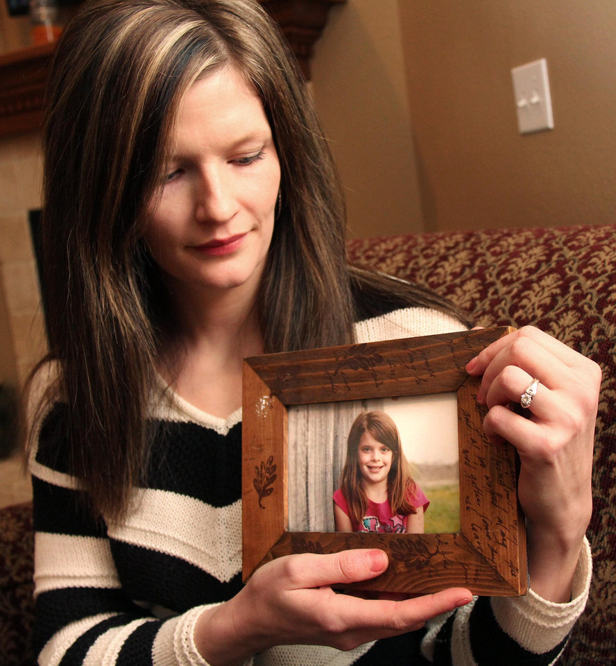 Photo - Erin Petersen holds a photo of her niece, Hailey Owens, Wednesday Feb. 19, 2014. A middle-school football coach has been jailed on suspicion of first-degree murder in the abduction and death of a 10-year-old girl in southwest Missouri, police said Wednesday. (AP Photo/The Springfield News-Leader, Christine Temple)