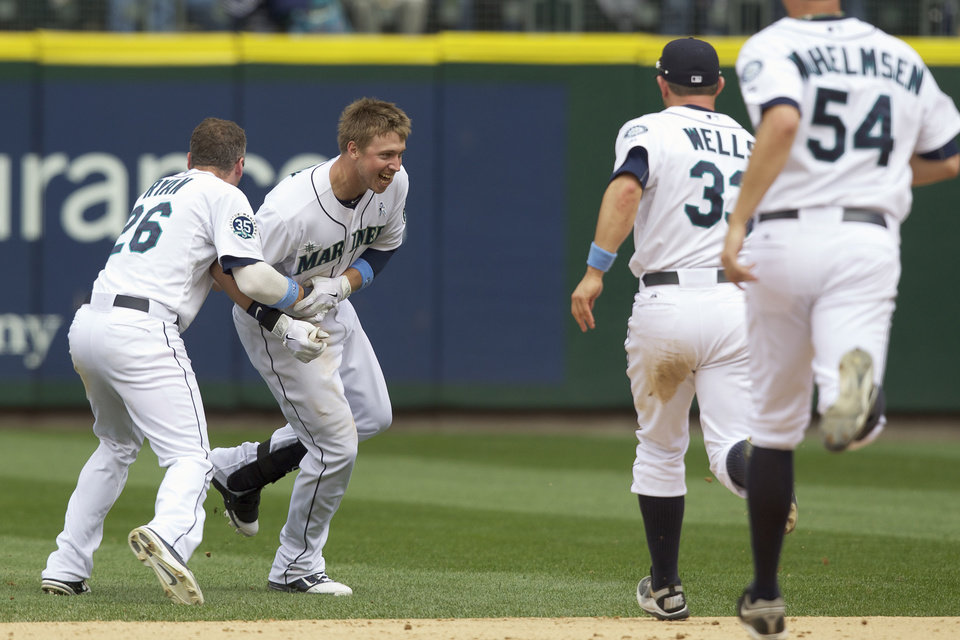 Photo -   Seattle Mariners' Justin Smoak, second from left, is mobbed by teammates Brendan Ryan, far left, Casper Wells, and Tom Wilhelmsen after hitting a game-winning single in the bottom of the ninth inning of a baseball against the San Francisco Giants game at Safeco Field in Seattle, Sunday June 17, 2012. The Mariners won the game 2-1. (AP Photo/Stephen Brashear)