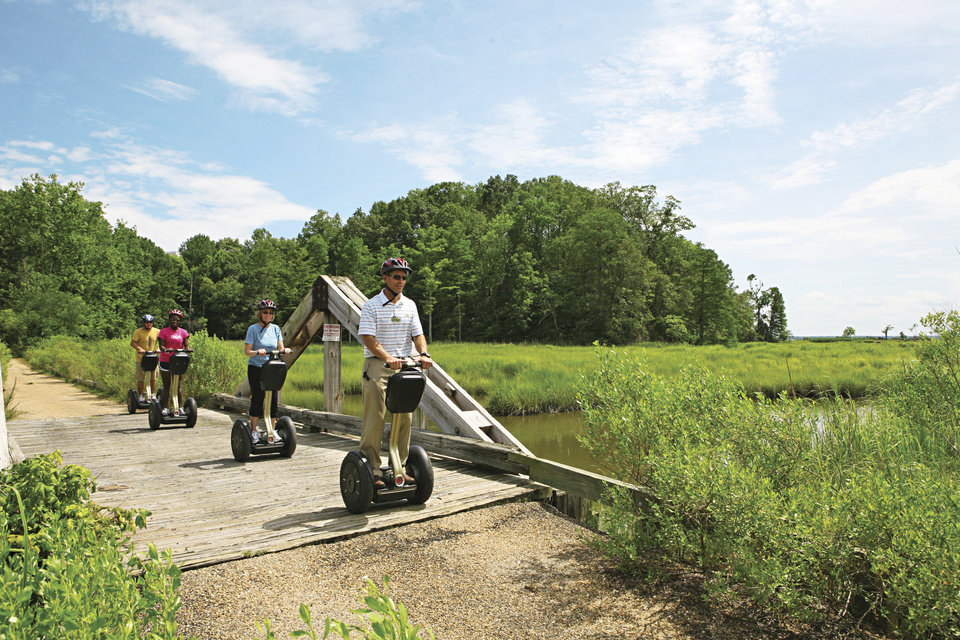 This July 2012 photo provided by Kingsmill Resort shows Kingsmill Resort�s director of sports, Kevin Dry, leading a Segway tour on the resort�s grounds in Williamsburg, Va. A number of hotels offer Segway tours as a novel way to see their grounds and nearby scenic areas. (AP Photo/Kingsmill Resort)