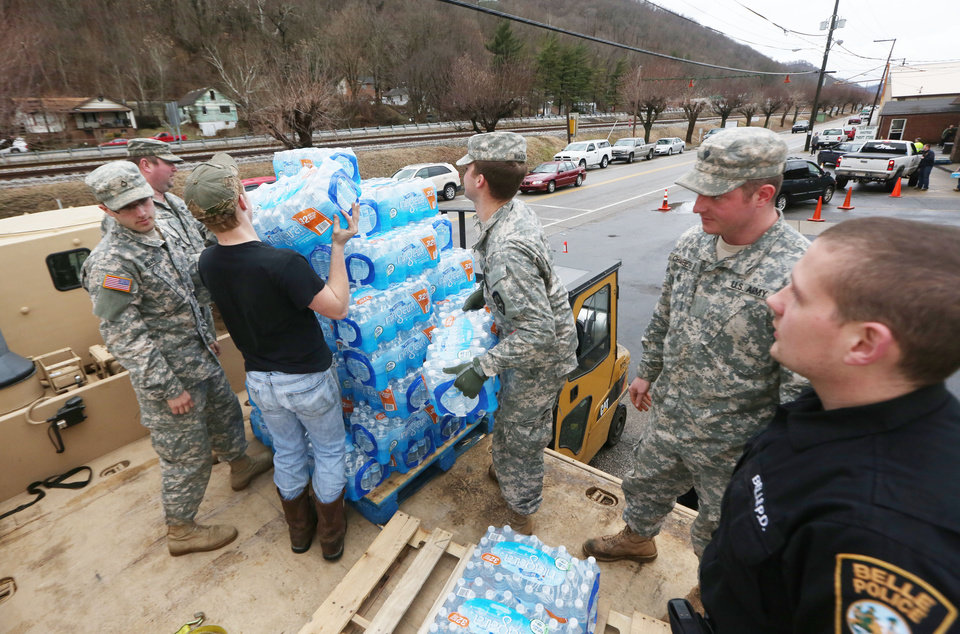 Photo - Members of the West Virginia Army National Guard, along with a member of the Belle Police Department and a volunteer, offload emergency water from a military truck to a forklift as citizens line up for water at the Belle Fire Department, Saturday, Jan. 11, 2014, in Belle, W.Va.  About 300,000 people Saturday entered their third day of not being able to take showers and wash clothes. Officials remain unclear when it might be safe again. Federal authorities began investigating how the foaming agent escaped the Freedom Industries plant and seeped into the Elk River. Just how much of the chemical leaked into the river was not yet known.  (AP Photo/The Daily Mail, Marcus Constantino)