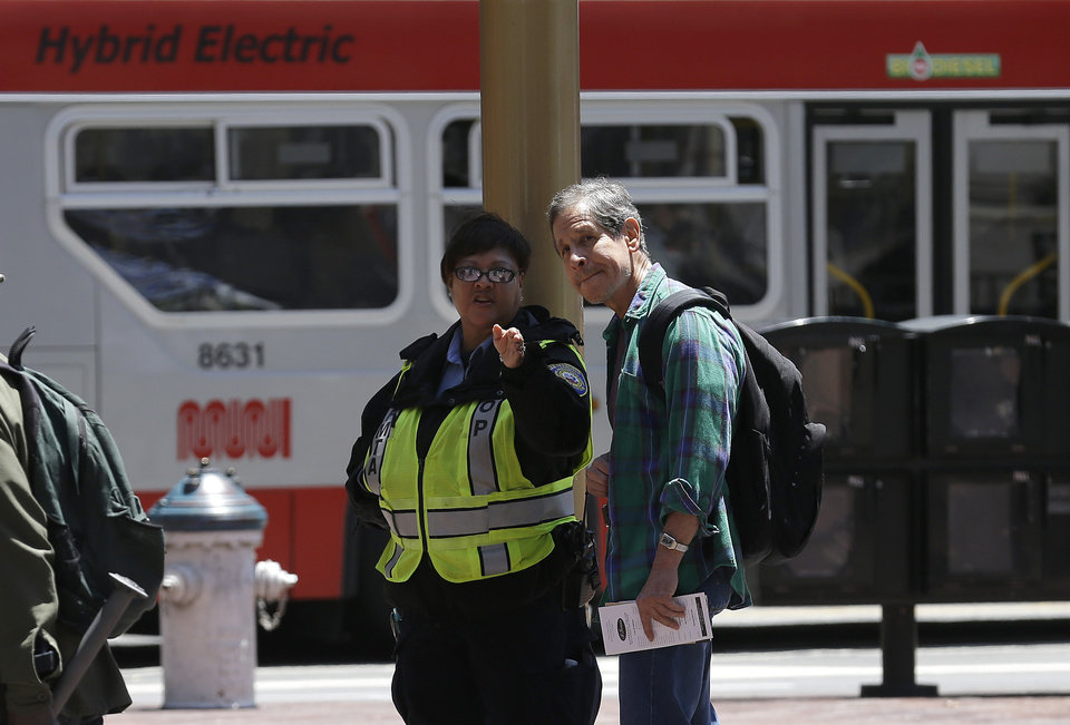 Photo - A San Francisco Municipal Transportation Agency fare inspector, left, speaks with a man at the Powell Street cable car turnaround in San Francisco, Tuesday, June 3, 2014. The city's famed cable cars were halted for a second straight day, and the rest of the transit system experienced delays after drivers called in sick again on Tuesday, days after overwhelmingly rejecting a new labor contract, officials said. (AP Photo/Jeff Chiu)