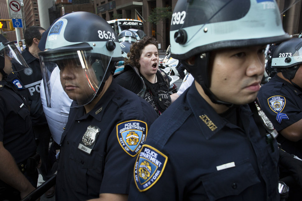 Photo -   A photographer is arrested during an Occupy Wall Street march as police stand guard, Monday, Sept. 17, 2012, in New York. A handful of Occupy Wall Street protestors have been arrested during a march toward the New York Stock Exchange on the anniversary of the grass-roots movement. (AP Photo/John Minchillo)