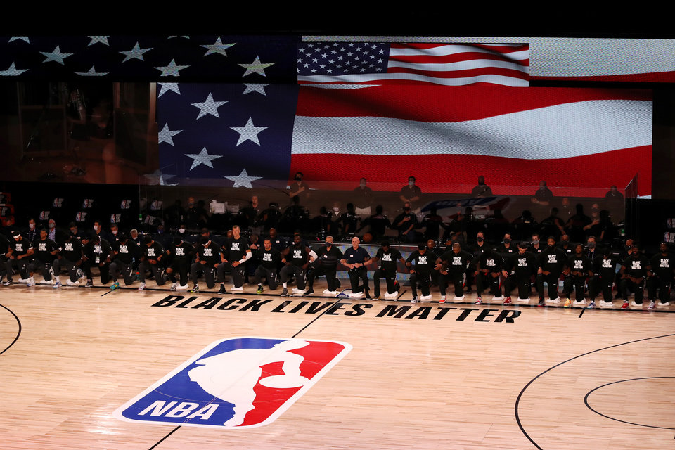 Photo - July 31, 2020; Lake Buena Vista, USA;  Players, coaches and staff kneel during the national anthem before the game between the Houston Rockets and the Dallas Mavericks at The Arena at ESPN Wide World Of Sports Complex on July 31, 2020 in Lake Buena Vista, Florida.  Mandatory Credit: Mike Ehrmann/Pool Photo via USA TODAY Sports
