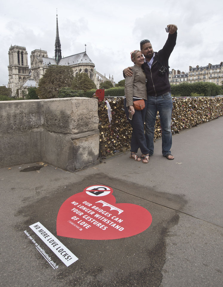Photo - Latvian's Regina and Vadim Medvedev from Riga, on honeymoon in Paris, pose for a selfie on the Pont de l'Archeveche in Paris next to a giant sticker in Paris, Wednesday, Aug. 13, 2014. Paris is hoping to persuade visiting couples to end the recent and unwelcome tradition of fixing padlocks to the Pont de l'Archeveche. With giant stickers in three languages in French, English and Spanish. Paris began its 'Lovewithoutlocks' campaign, saying the city's famed bridge could not withstand the thousands of padlocks that cling to every available surface. (AP Photo/Michel Euler)