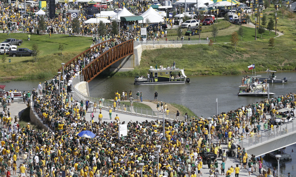 Photo - Fans walks across the Brazos River as they head to the new McLane Stadium before an NCAA college football game between SMU and Baylor Sunday, Aug. 31, 2014, in Waco, Texas. (AP Photo/LM Otero)
