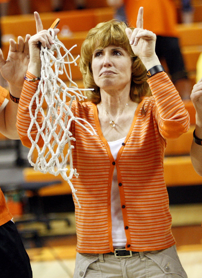 Photo - Shelley Budke, widow of OSU head coach Kurt Budke, points up at the end of the singing of the alma mater after the OSU Cowgirls won the Women's NIT championship college basketball game between Oklahoma State University and James Madison at Gallagher-Iba Arena in Stillwater, Okla., Saturday, March 31, 2012. Kurt Budke and three others were killed in a plane crash on a recruiting trip in November of 2011. OSU won, 75-68. Photo by Nate Billings, The Oklahoman