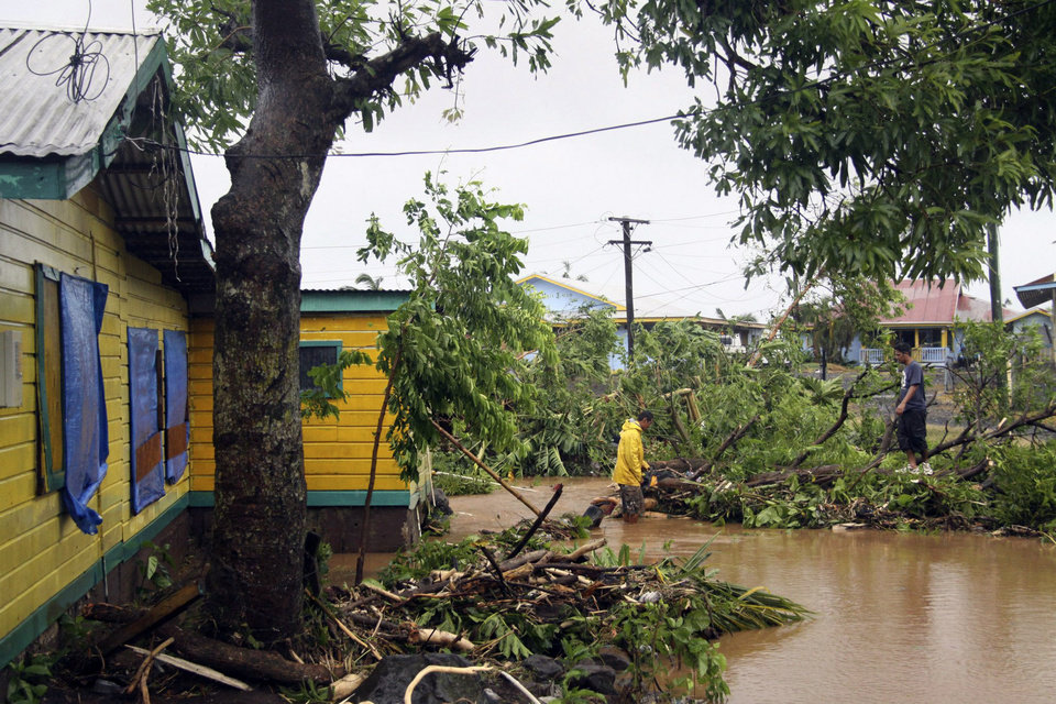 A man wades through deep water in Samoa's capital Apia, Friday, Dec. 14, 2012, after cyclone Evan ripped through the South Pacific island nation.  The powerful cyclone flattened homes and uprooted trees with winds of up to 165 kilometers (100 miles) per hour. Phone lines, Internet service and electricity were down across the country, and the airport was closed. (AP Photo/Seti Afoa)